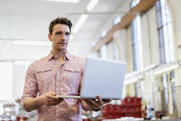 Man using laptop in factory - DIGF06313