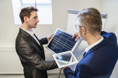 Two businessmen in office with solar cell and tablet discussing - DIGF06319