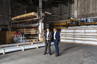 Two businessmen with folder talking in an old storehouse - DIGF06325