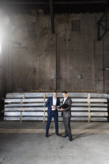 Two businessmen with folder talking in an old storehouse - DIGF06328