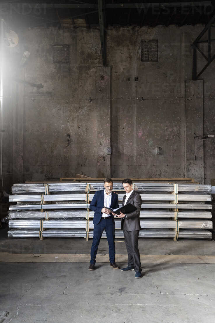 Two businessmen with folder talking in an old storehouse - DIGF06328 - Daniel Ingold/Westend61