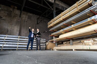 Two businessmen with folder talking in an old storehouse - DIGF06331