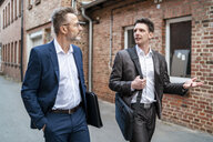 Two businessmen walking and talking at an old brick building - DIGF06334