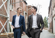 Two smiling businessmen walking and talking at an old brick building - DIGF06337