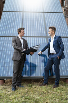 Two businessmen talking at solar panels - DIGF06340