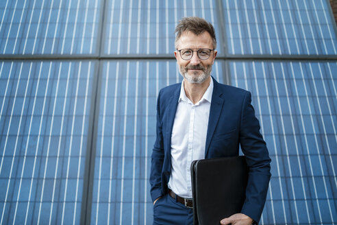 Portrait of smiling businessman holding folder standing in front of solar panels - DIGF06346