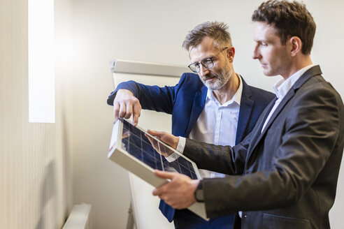 Two businessmen in office with solar cell discussing - DIGF06379