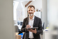 Smiling businessman using tablet in office - DIGF06394