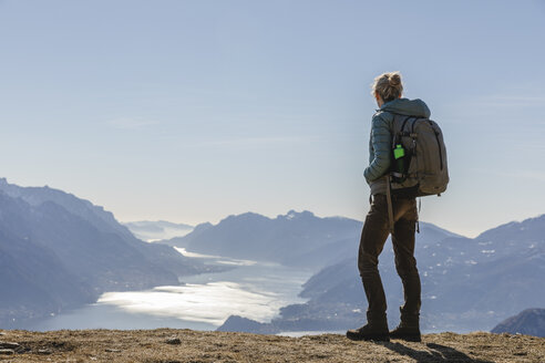 Female hiker looking at the lake landscape from the mountain. Como, Lecco. - MRAF00370