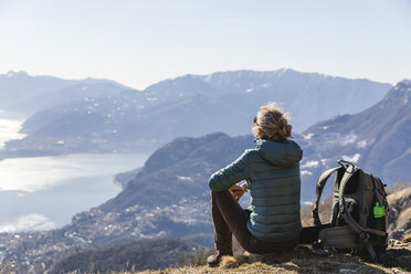 Italy, Como, Lecco, woman on a hiking trip in the mountains above Lake Como sitting down enjoying the view - MRAF00373