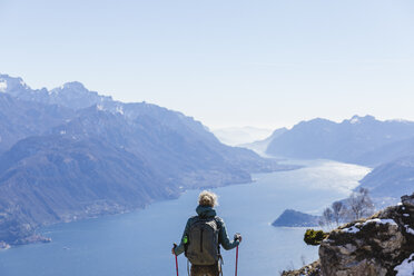 Italy, Como, Lecco, woman on a hiking trip in the mountains above Lake Como enjoying the view - MRAF00382