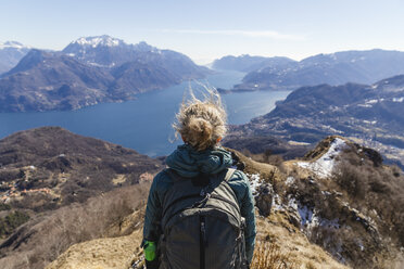 Italy, Como, Lecco, woman on a hiking trip in the mountains above Lake Como enjoying the view - MRAF00391