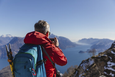 Italy, Como, man on a hiking trip in the mountains above Lake Como taking photo with cell phone - MRAF00397
