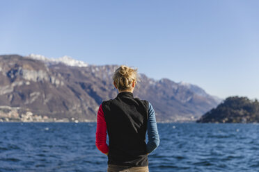 Italy, Como, rear view of woman enjoying the view of Lake Como - MRAF00400