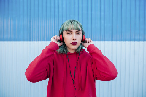 Portrait of young woman with blue dyed hair listening music with headphones - LOTF00063