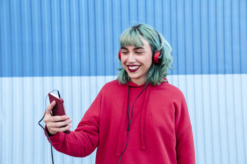 Portrait of laughing young woman with blue dyed hair with headphones taking selfie with mobile phone - LOTF00066