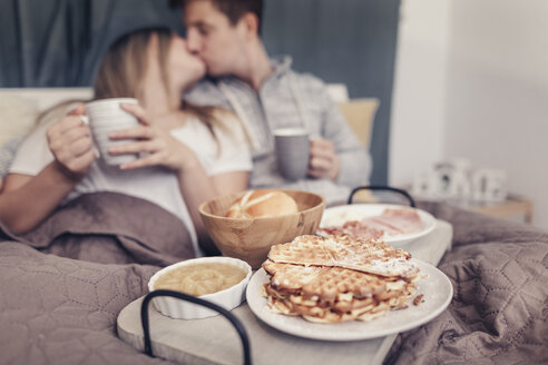Affectionate young couple having breakfast in bed - SEBF00081