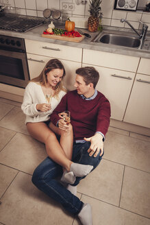 Young couple sitting on kitchen floor and drinking champagne - SEBF00099