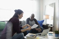 Couple at laptop discussing paperwork paying bills online in living room - HEROF30405