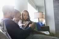 Family using digital tablet on living room sofa - HEROF30420
