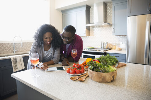 Couple drinking sangria and using digital tablet in kitchen - HEROF30423