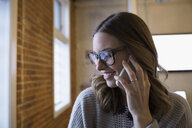 Close up businesswoman wearing eyeglasses talking on cell phone - HEROF30486