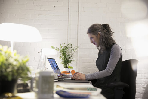 Businesswoman working at laptop in office - HEROF30489