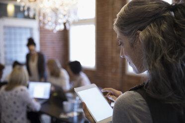 Businesswoman using digital tablet in meeting - HEROF30498