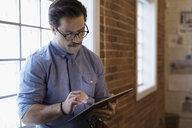 Businessman using digital tablet in office - HEROF30513