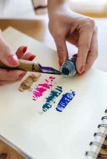 Woman's hand applying colour pigments at colouring book - MGOF03982