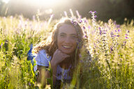 Portrait of happy woman lying on flower meadow at evening twilight - SARF04172