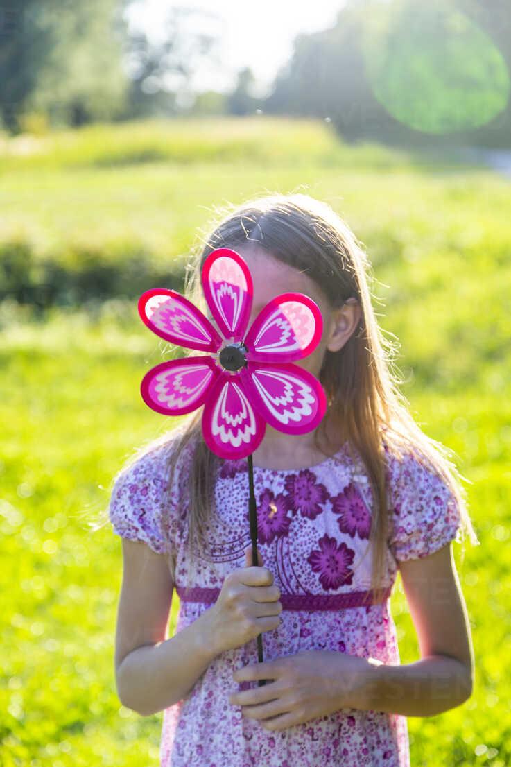 Girl hiding her face behind pinwheel - SARF04175 - Sandra Roesch/Westend61