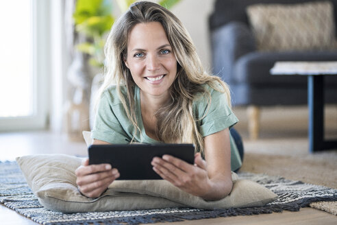 Portrait of smiling woman lying on the floor at home using tablet - SBOF01910