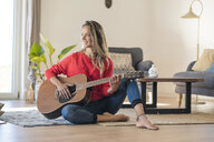 Smiling woman sitting on the floor at home playing guitar - SBOF01922