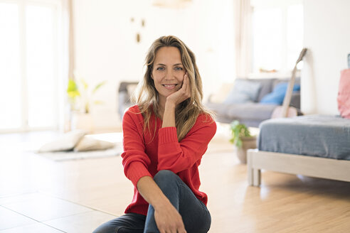 Portrait of smiling woman sitting on the floor at home - SBOF01925