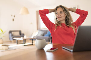 Woman sitting at dining table at home having a break from her work at the laptop - SBOF01934