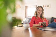 Portrait of smiling woman with laptop and cell phone on dining table at home - SBOF01937