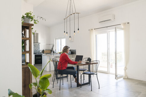 woman with red pullover working on her laptop in home office in contemporary modern living room and kitchen - SBOF01955