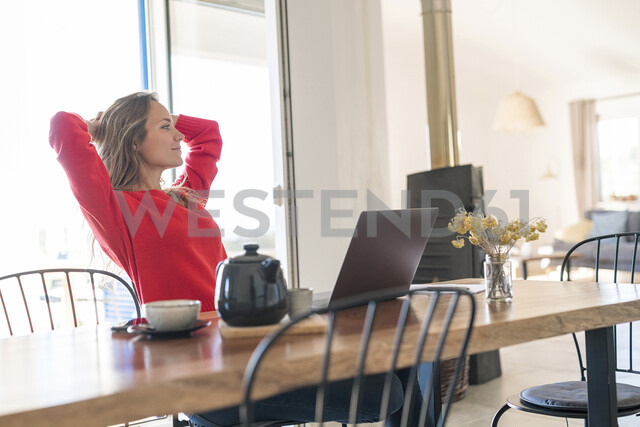 Woman with laptop on dining table at home having a break - SBOF01958 - Steve Brookland/Westend61