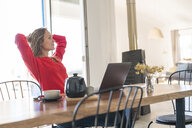 Woman with laptop on dining table at home having a break - SBOF01958