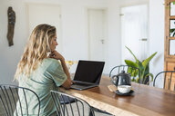 Woman using laptop on dining table at home - SBOF01961