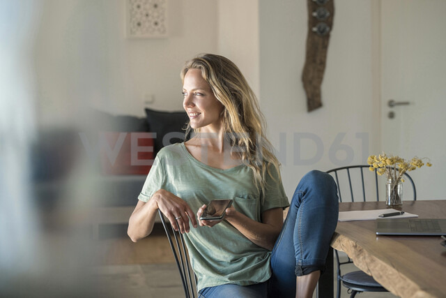 Smiling woman with cell phone and laptop on dining table at home - SBOF01964 - Steve Brookland/Westend61