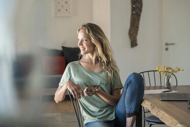 Smiling woman with cell phone and laptop on dining table at home - SBOF01964