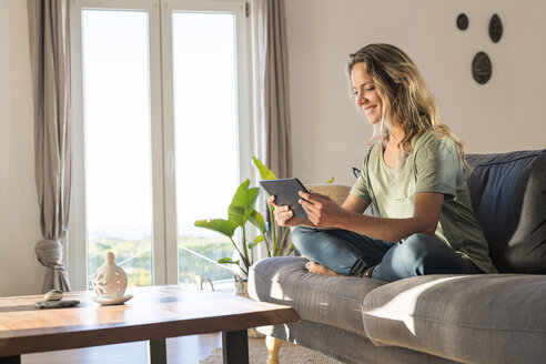 smiling blonde woman relaxing on couch holding tablet in modern contemporary living room - SBOF01967