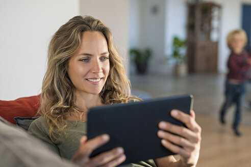 Smiling woman realxing on couch at home using tablet with son in background - SBOF01970