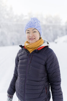 Finland, Kuopio, portrait of smiling woman in winter landscape - PSIF00247