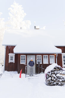 Finland, Kuopio, woman standing in front of farmhouse in winter - PSIF00250