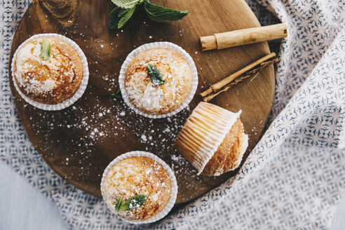 Home-baked muffins with cinnamon and mint on wooden board - ERRF00813