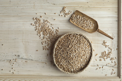 Organic spelt wheat in bast bowl, on wood, from above - ASF06328