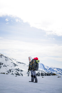 Young man with backpack, snowcapped mountains in the background - ACPF00499